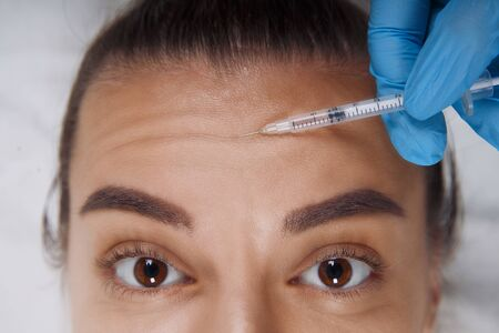 Closeup Portrait of young Caucasian woman getting cosmetic injection in forehead. People, cosmetology, plastic surgery and beauty concept. Stock Photo