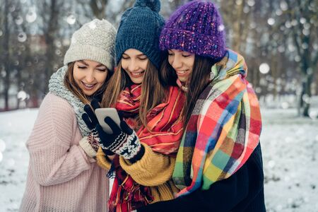 Three women friends outdoors in knitted hats using mobile phone on a snowy cold weather. Group of young female friends outdoors in winter park.