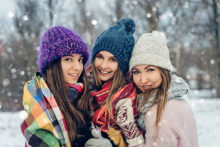 Three women friends outdoors in knitted hats having fun on a snowy cold weather. Group of young female friends outdoors in winter park.