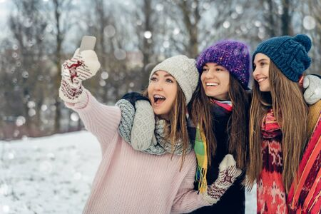 Three women friends outdoors in knitted hats using mobile phone on a snowy cold weather. Group of young female friends enjoying taking selfies outdoors in winter park.