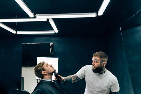 Tattooed Barber trimming bearded man with shaving machine in barbershop. Hairstyling process. Hairstylist cutting the beard of a bearded male.