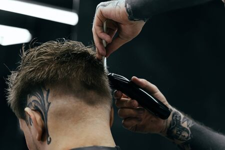 Male haircut with electric razor. Tattooed Barber makes haircut for client at the barber shop by using hairclipper. Man hairdressing with electric shaver.