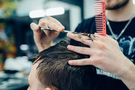 Tattooed Barber cuts the hair of the client with scissors. Close up. Attractive male is getting a modern haircut in barber shop. Close up view.