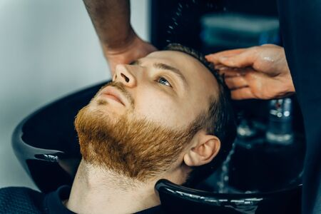 Attractive male is getting a modern haircut in barber shop. Top view of a young man getting his hair washed and his head massaged in a hair salon Imagens