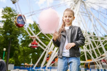 Portrait of a child with sweet cotton candy. A little girl on the background of ferris wheel is eating candy-floss summer sunny day.