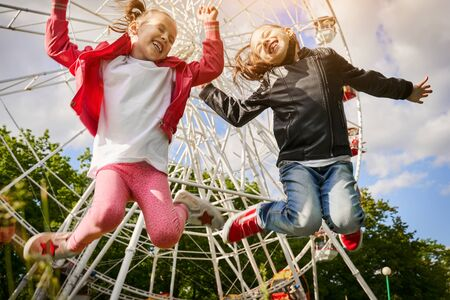Two Girls Are having fun in amusement park. A Ferris Wheel Are On The Background.
