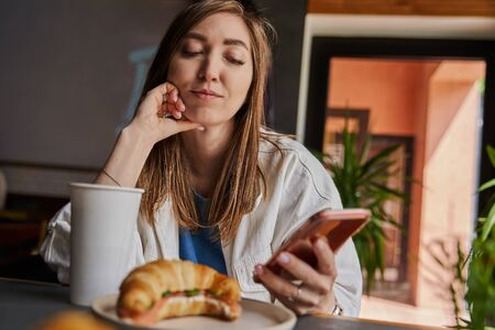 Front view of attractive woman wearing glasses using smartphone, drinking coffee in cafe. Female texting and sharing messages on social media, enjoying mobile technology, relaxing in coffee shop.