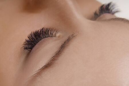 Eyelash Extension Procedure. Close up view of beautiful female eye with long eyelashes, smooth healthy skin