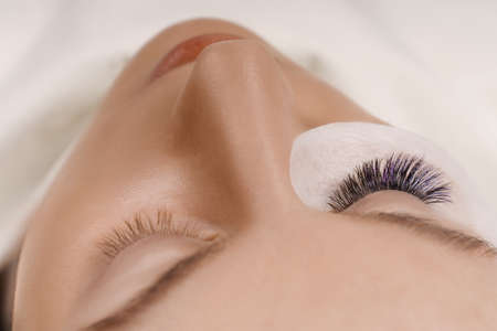 Eyelash Extension Procedure. Close up view of beautiful female eye with long eyelashes, smooth healthy skin. Banco de Imagens
