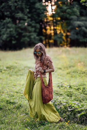 Beautiful young woman wearing bohostyle clothes posing in the rays of the evening sun, sunset. Boho style fashion, female wearing silver jewelry having fun in park outdoors.