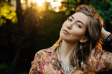 Close up Beautiful young woman wearing bohostyle clothes posing in the rays of the evening sun, sunset. Boho style fashion, female wearing silver jewelry having fun in park outdoors.