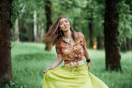 Portrait of Beautiful young woman wearing bohostyle clothes posing in the rays of the evening sun, sunset. Boho style fashion, female wearing silver jewelry having fun in park outdoors.