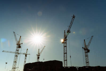 Industrial construction cranes and building silhouettes over sun at sunrise or sunset.