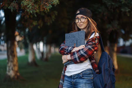 Happy Young female student dressed in casual clothing with cup of coffee and backpack behind her back walking around city. Woman student holding laptop and drinking coffee. Summer sunset time.