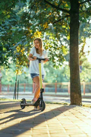 Smiling woman rides electric scooter or e-scooter in city park at sunset. Female using electric transport in urban park Фото со стока