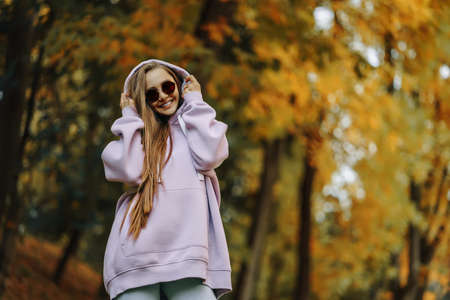 Beautiful happy smiling young woman wearing pink hoodie walking in autumn park. Season and people concept.