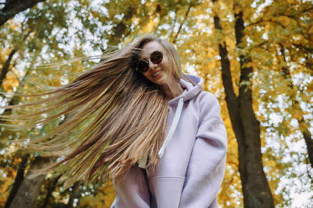 Young woman wearing pink hoodie and jeaans having fun in the park at sunny autumn day. Season and people concept. Фото со стока