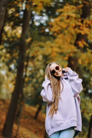 Young woman wearing pink hoodie and jeaans in the park at sunny autumn day. Season and people concept.