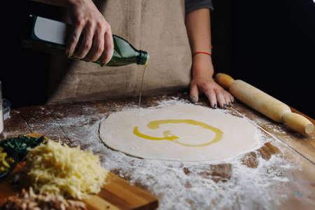 Home Made Pizza Cooking. Woman hand cook pouring olive oil on dough. Food preparing concept under quarantine due to epidemic.