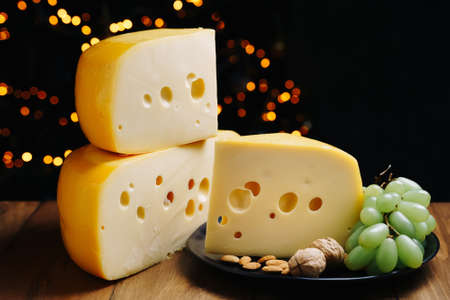 Cheese on table with grapes and nuts. Medium hard cheese head edam, gouda, parmesan on wooden board. Healthy eating concept. 免版税图像 - 163352359