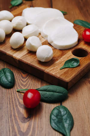 White small mozzarella cheese balls, spinach leaves and tomatoes on wooden board. Reklamní fotografie