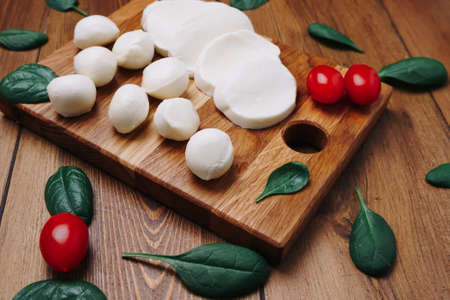 White small mozzarella cheese balls, spinach leaves and tomatoes on wooden board. 免版税图像