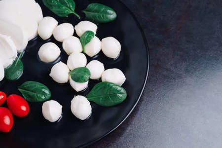 White small mozzarella cheese balls, spinach leaves and tomatoes on black plate.