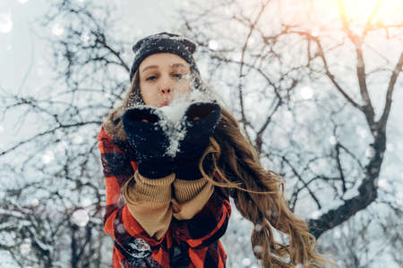 Woman Wearing Warm Winter Clothes And Hat Blowing Snow In Winter Park. Flying Snowflakes. Sunny day. Joyful Beauty young girl Having Fun in frosty Forest.
