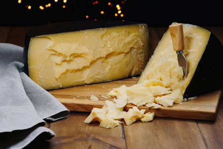Medium hard cheese head parmesan on wooden board, with cheese parmesan knifes. 免版税图像 - 164774327