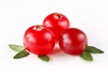 cranberry fruit: Fresh red cranberries with leaves on a white.