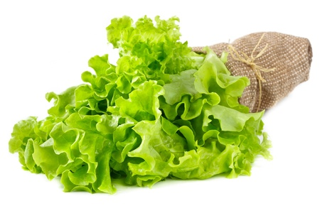 Bunch of fresh green salad leaves in a fabric bag on white. photo