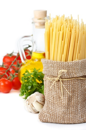 Spaghetti on fabric bag, olive oil, tomatoes and parsley on white. photo