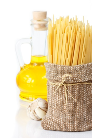 Italian spaghetti on bag, olive oil and garlic on white. photo