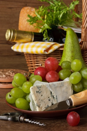 Grapes, cheese, pear and bottle of wine. photo