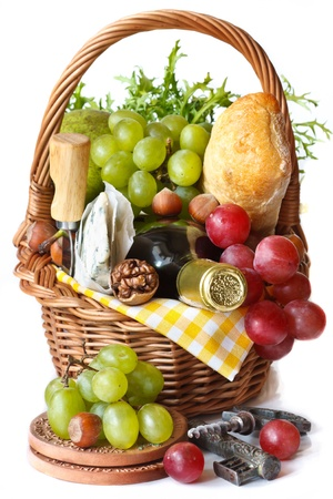 Grapes, wine, nuts, cheese and ciabatta in a wicker basket. photo