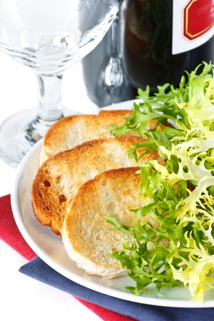 escarole: Crusty toastes, bottle of red wine and endive salad. Stock Photo