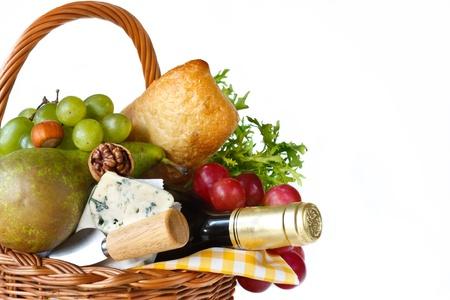 canasta de frutas: Vino, tosta, queso, hierbas, uvas y peras en una canasta de mimbre para picnic.