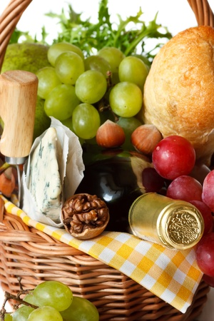 Wine, ciabatta, cheese, herbs, grapes and pear in a wicker basket for picnic close-up. photo