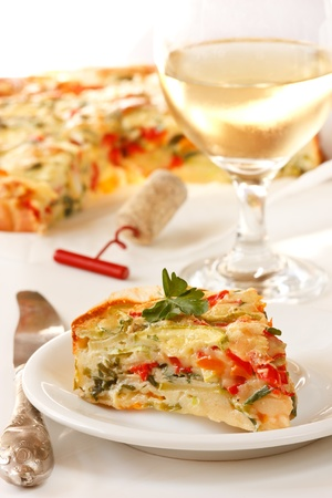 Tasty vegetables pie on a plate and glass of wine. photo