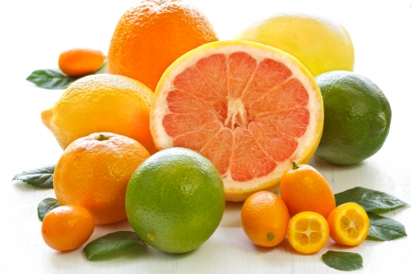 citrus: Fresh citrus fruit with leaves on a white garden board.