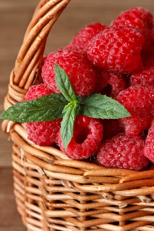 Fresh sweet raspberries with water drops in a wicker basket close-up. photo