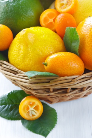 Fresh citrus fruit with leaves in a wicker basket close-up. photo