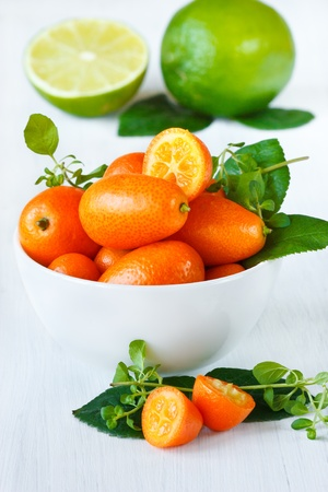 Delisious kumquats in a white ceramic bowl on a garden board. photo