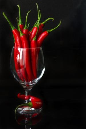 pepe nero: Hot chili in un bicchiere di vino su uno sfondo nero. Archivio Fotografico