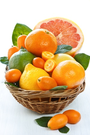 Fresh citrus fruit with leaves in a wicker basket. Stock Photo - 10439605
