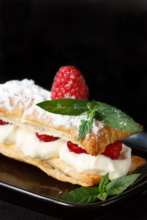 sweet pastry: Mille feuille with whipped sour cream and raspberries.. Stock Photo