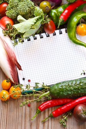 culinary: Open notebook and fresh garden vegetables and herbs.