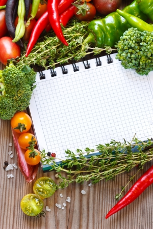 vegetarian: Open notebook and fresh vegetables on an old wooden board.