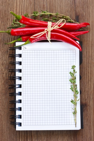 cookbook: Notebook with red chili and thyme on a wooden board.