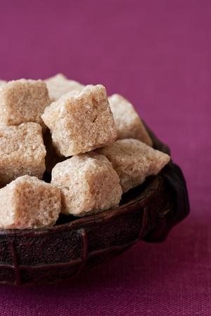 Cubes of brown sugar in a ceramic bowl. photo